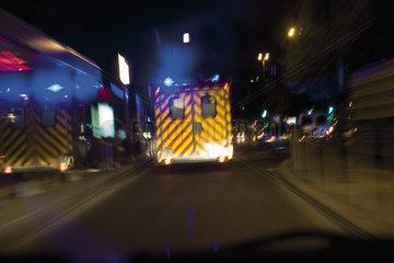 Ambulance driving on street at night