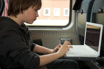 Junge im Zug mit Notebook