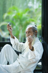 Elderly man wearing traditional Chinese clothing  listening to MP3 player  moving arms and smiling