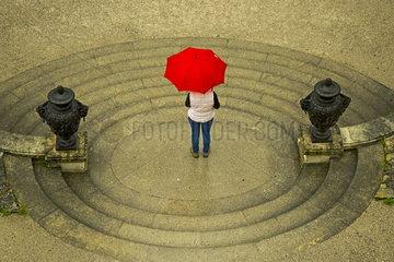 Eine Frau unter einem roten Regenschirm