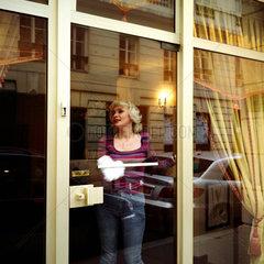 Paris  eine Frau putzt ein Schaufenster