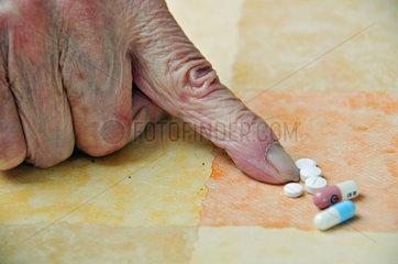 83jaehrige Frau mit ihren taeglichen Medikamenten