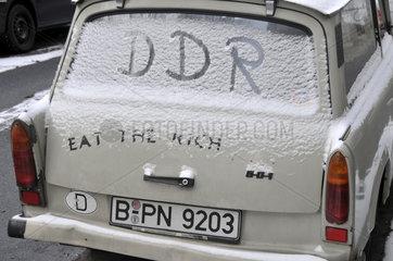 Trabant mit dem gemalten DDR-Kuerzel in der schneebedeckten Scheibe