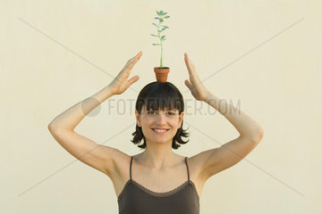 Woman balancing small potted plant on head  smiling at camera  portrait