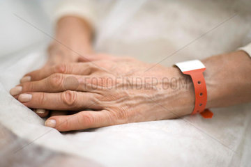 Hospital patient's hands folded in lap  close-up