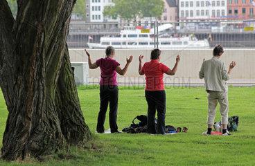 Drei meditierende Frauen am Koelner Rheinufer