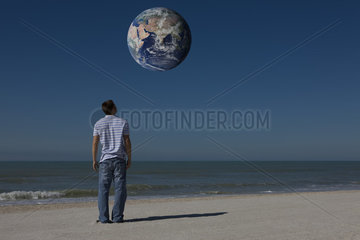 Man on beach looking up at planet earth orbiting overhead