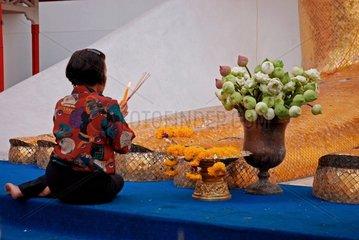 Glaeubige Buddhistin vor einer Buddhastatue