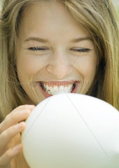 Young woman blowing up balloon  laughing  close-up