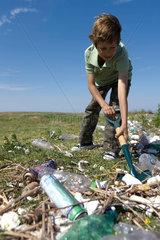 Boy shoveling trash in field