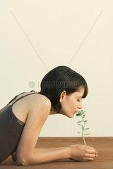 Woman smelling sedum plant  eyes closed  side view