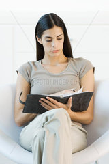 Woman sitting in chair  turning the page of her journal