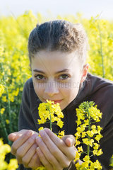 Teen girl in field of yellow flowers  leaning forward to smell blossom  smiling at camera