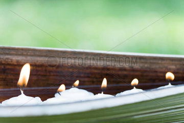 Lit votive candles in natural setting