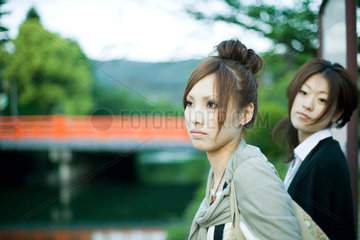 Young females outdoors  looking away  bridge in background