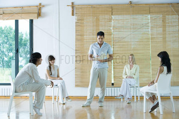Man leading group therapy session  taking notes