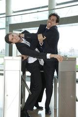 Businessmen fighting to beat each other through turnstile