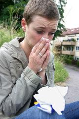 Frau putzt sich die Nase mit einemTaschentuch