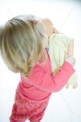 Blonde toddler girl holding baby doll