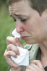 Jammernde Frau putzt sich die Nase