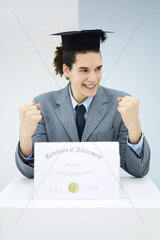 Young man with diploma  wearing graduation cap  smiling and clenching fists