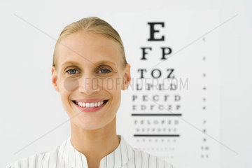 Young woman  eye chart in background  portrait