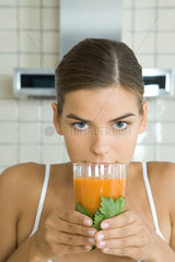 Woman with glass of fresh carrot juice