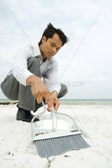 Man crouching on beach  sweeping sand into dustpan  low angle view