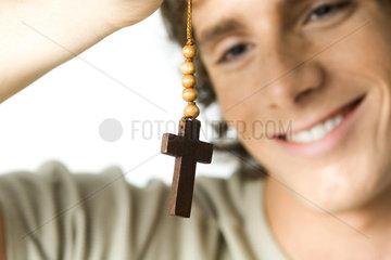 Young man looking at cross  smiling  close-up