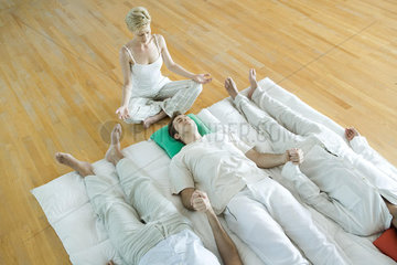 Alternative therapy session  three adults lying side by side while therapist sits nearby