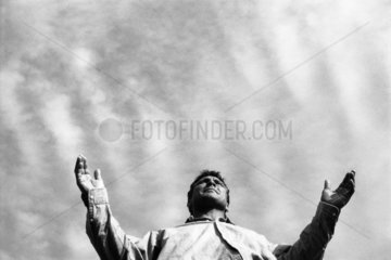 Man standing with arms out  low angle view