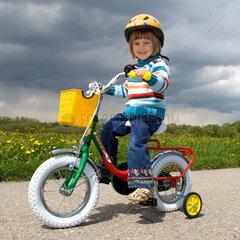 Ein Maedchen faehrt mit ihrem Fahrrad auf der Landstrasse