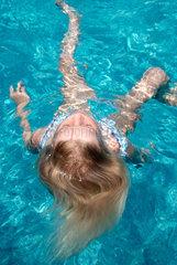 Berlin  Maedchen schwimmt auf dem Ruecken im Pool