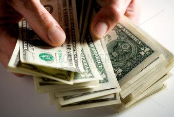 Berlin  in der Hand gehaltene aufgefaecherte Dollarscheine