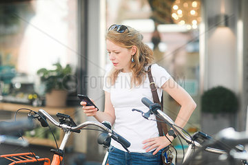Germany  young woman with smartphone renting a city bike