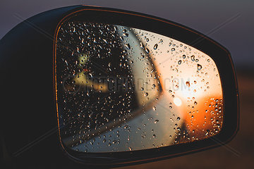 Raindrops reflecting on rear-view mirror of car during sunset