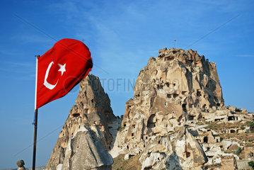 Tuerkische Nationalflagge vor dem Burgberg von Uchisar in Kappadokien