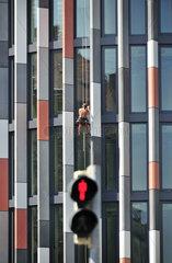 Rote Ampel vor avantgardistischer Fassade mit Fensterputzer