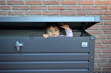 Kleines Maedchen schaut aus einer Kiste