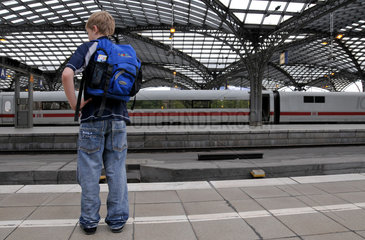 Alleinreisender Junge warten auf Zug im K__lner Hauptbahnhof