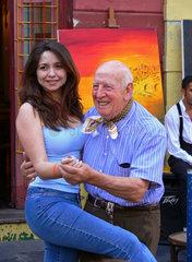 Argentinien: Strassenmaler und Touristin tanzen Tango