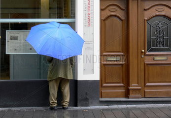 Zeitungsleser unterm Regenschirm