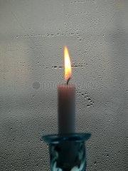 brennende Kerze vor beschlagener Fensterscheibe