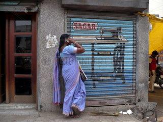 Indische Frau im Sari telefoniert mit ihrem Handy