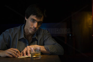 Man sitting in bar with pen  notebook and glass of whiskey  looking at camera