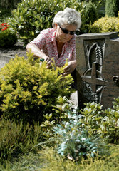 Frau pflegt ein Grab