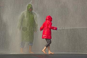 Mann mit Regenkleidung im Wasserschauer
