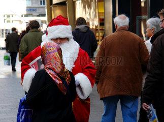 Weihnachtsmann im Gespraech muslimischer Frau