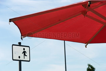 Sonnenschirm und Spielplatzschild auf einer Autobahnraststaette
