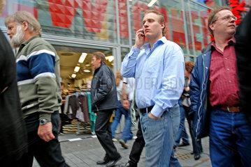 Mann mit Handy in der Koelner Innenstadt